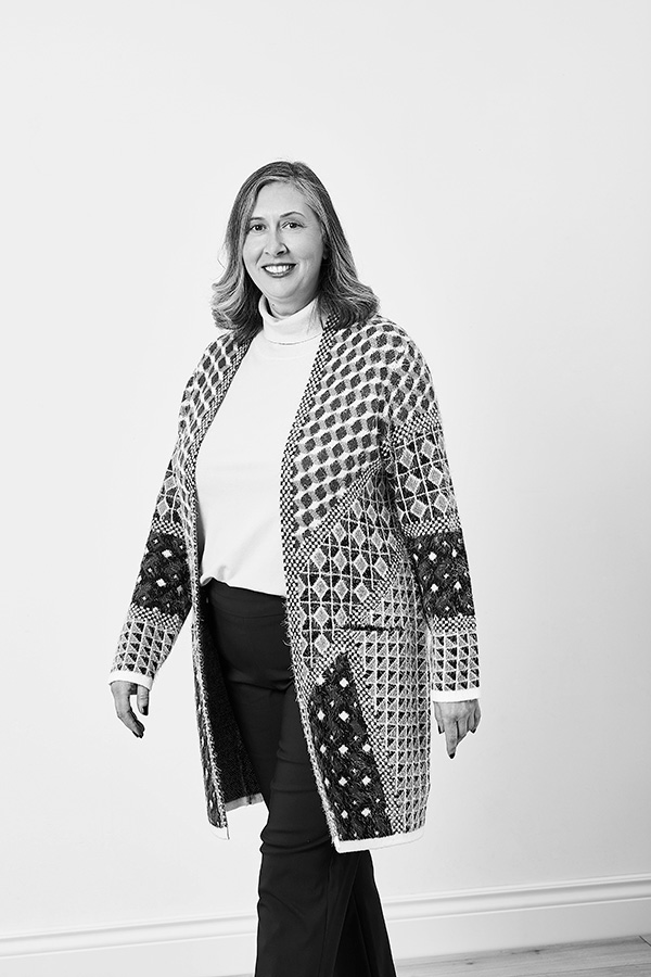 linda stands against a white background. She is smiling at the camera and wearing a long cardigan